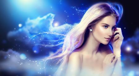 polvo: Chica de ensue�o belleza con el pelo largo que sopla sobre el cielo nocturno Foto de archivo