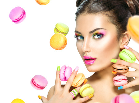 Beauty fashion model girl taking colorful macaroons Stockfoto