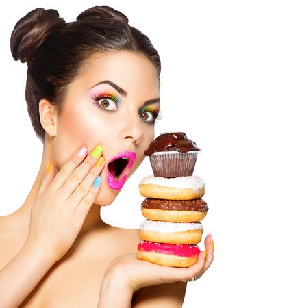 food: 美容時尚型的女孩服用甜食和豐富多彩的甜甜圈
