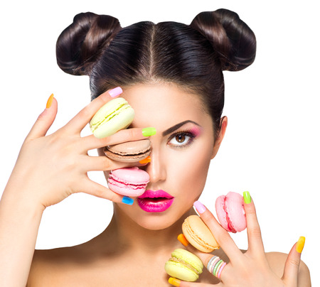 sweet: Beauty fashion model girl taking colorful macaroons Stock Photo