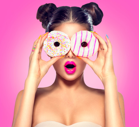 junk: Beauty model girl taking colorful donuts. Dieting concept Stock Photo