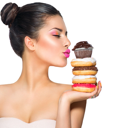 junk: Beauty fashion model girl taking sweets and colorful donuts Stock Photo