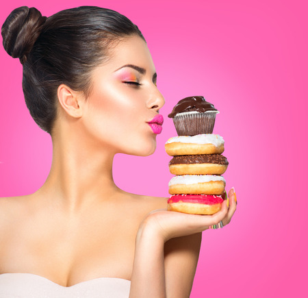 unhealthy diet: Beauty fashion model girl taking sweets and colorful donuts Stock Photo