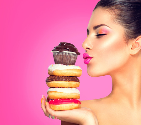 Beauty fashion model girl taking sweets and colorful donuts 스톡 콘텐츠