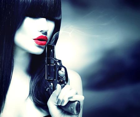 junge nackte m�dchen: Reizvolle vorbildliche Frau mit einer Pistole. Schwarzweiss-Portrait Lizenzfreie Bilder