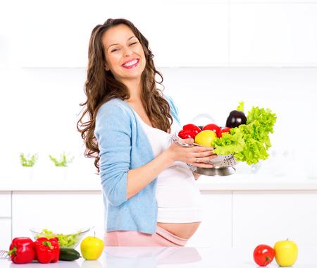 Embarazadas jóvenes verduras mujer cocina. La comida sana