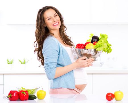 étel: Terhes fiatal nő főzés zöldség. Egészséges étel Stock fotó