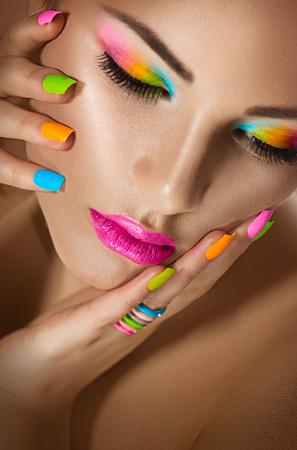 pesta�as postizas: Retrato de la muchacha atractiva con maquillaje viva y colorida nailpolish