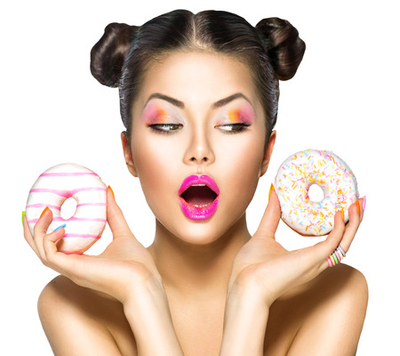 Beauty model girl taking colorful donuts. Dieting concept 스톡 콘텐츠