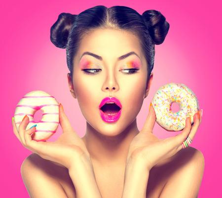 Beleza moda modelo menina que toma doces e donuts coloridos
