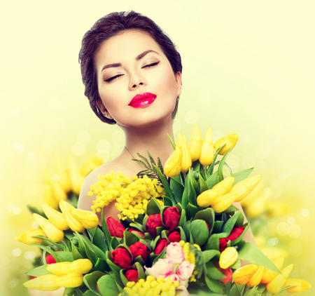 make a gift: Beauty model woman with spring flower bouquet Stock Photo
