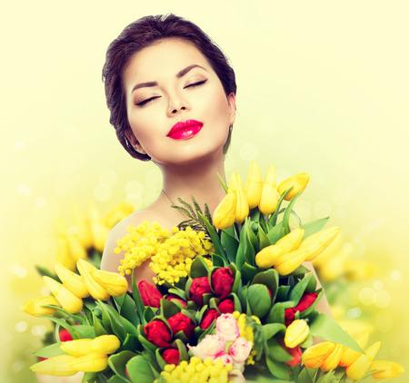 Schoonheid model vrouw met lente boeket bloemen Stockfoto