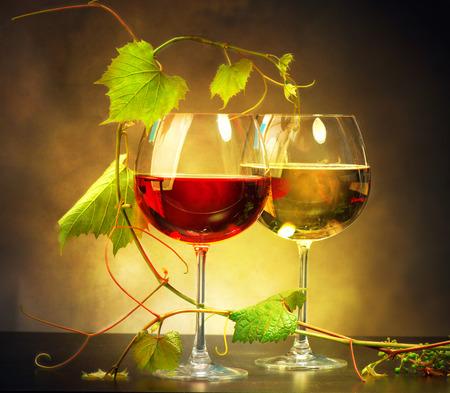 Dwie lampki wina ozdobione liśćmi winogron