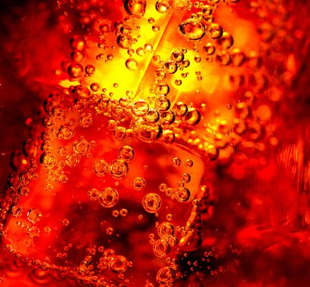 fizzy: Cola background. Cola with Ice and bubbles in glass closeup