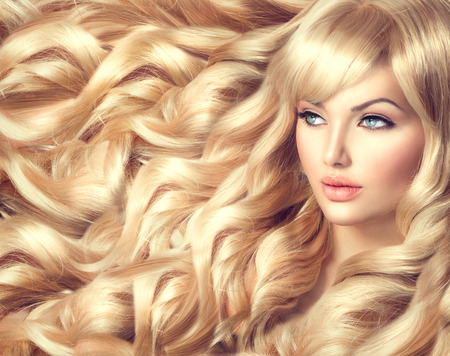 hairdressing: Beautiful model girl with long curly blond hair