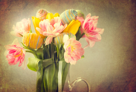 Easter. Tulip flowers bouquet decorated with colourful eggs photo