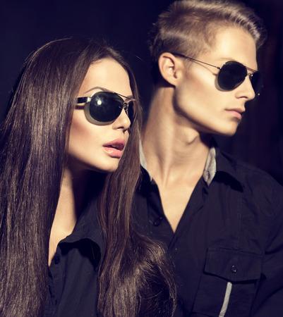 Мода модели пара носить солнцезащитные очки на темном фоне