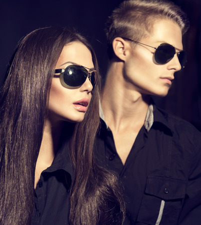 trendy: Fashion models couple wearing sunglasses over dark background