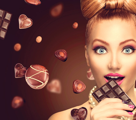 Beauty fashion model girl eating chocolate