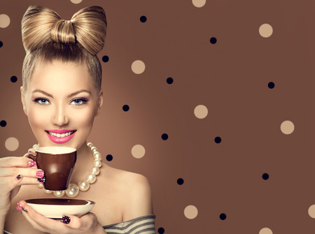 Retro styled model girl drinking coffee or tea