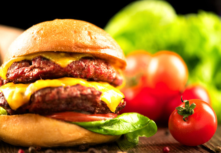 Cheeseburger with fries on wooden table photo