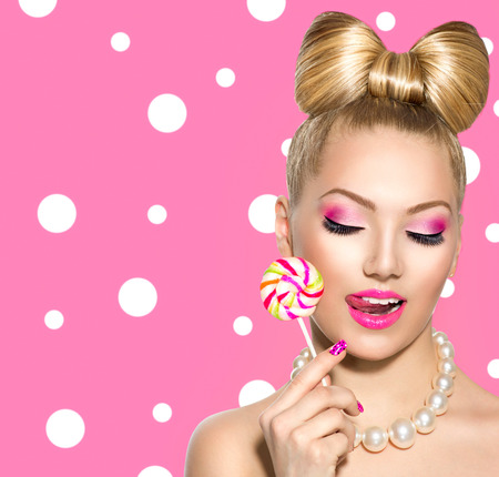 Beauty girl eating colourful lollipop over polka dots background photo