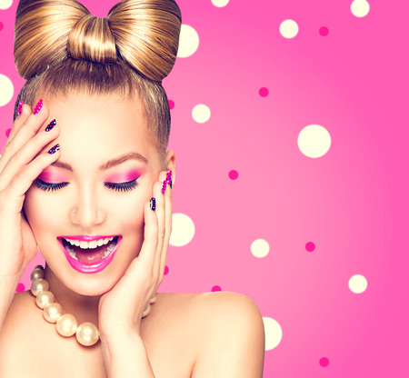 pink nail polish: Beauty model girl with bow hairstyle over polka dots background