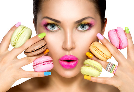 makeup: Beauty fashion model girl taking colorful macaroons Stock Photo