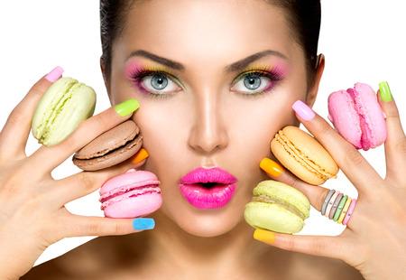 lapiz labial: Modelo de manera de la belleza joven de tomar macarrones de colores