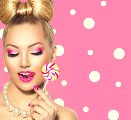 candies: Beauty fashion model girl eating colorful lollipop