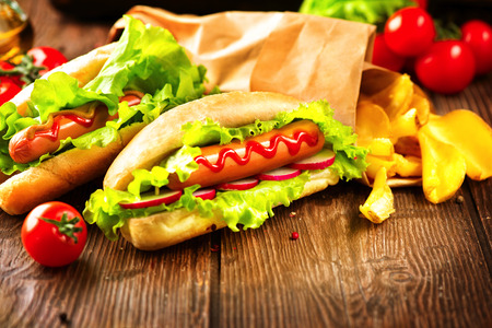 perro comiendo: Pancho. A la parrilla perros calientes con salsa de tomate en una mesa de madera Foto de archivo