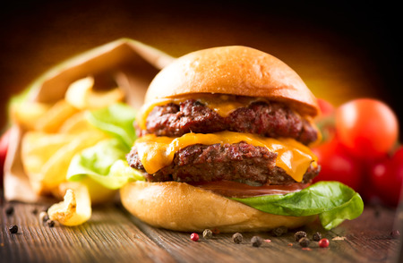 Cheeseburger with fresh salad and french fries on a wooden table photo