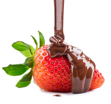 Melted chocolate pouring on fresh ripe juicy strawberry