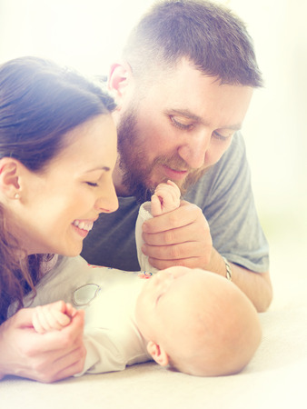 Happy family - mom, dad and their newborn baby photo