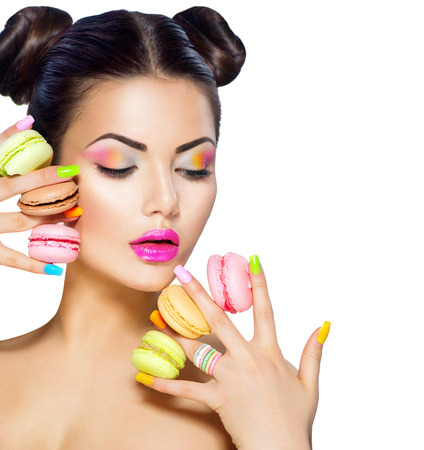 Beauty fashion model girl taking colorful macaroons Stock Photo