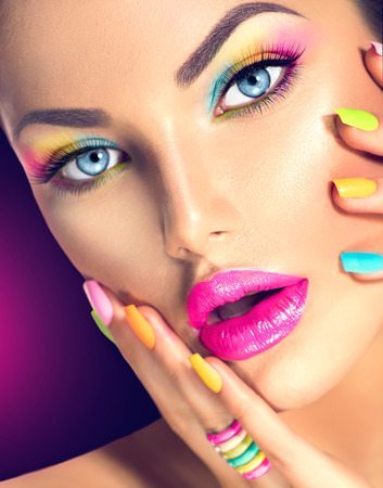 makeup fashion: Beauty girl face with vivid makeup and colorful nail polish