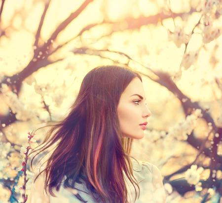 Prachtige model meisje met lange haren waait in de lentetuin