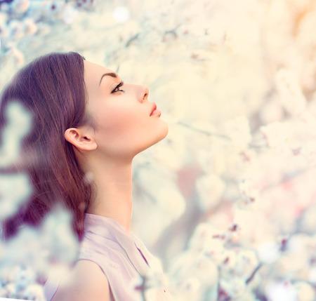 美女: 春季時尚女孩戶外人像在樹上綻放