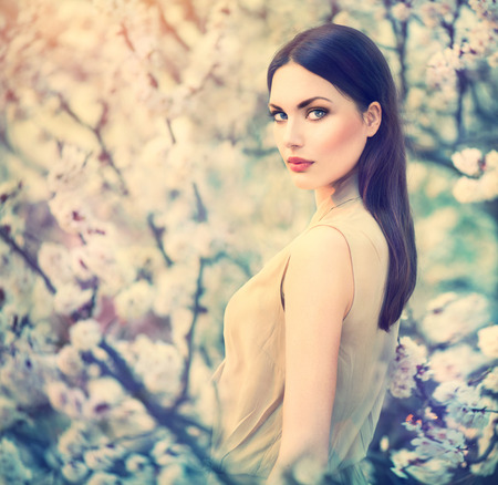 beauty make up: Fashion girl outdoor portrait in spring blooming trees