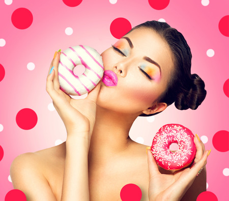 sexy kiss: Beauty fashion model girl taking colorful donuts over pink