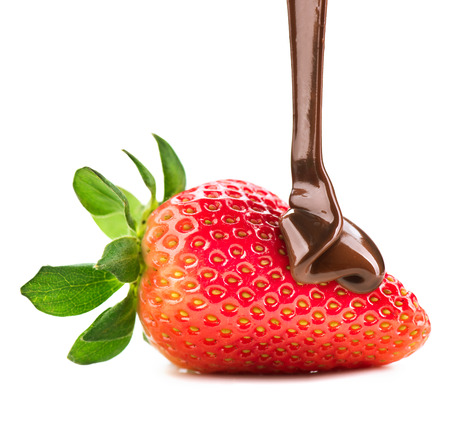 Melted chocolate pouring on fresh ripe juicy strawberry photo