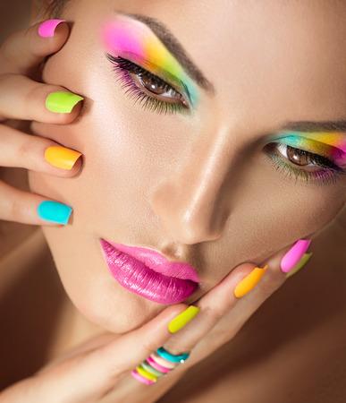 Cara de niña de belleza con maquillaje vivo y colorido esmalte de uñas