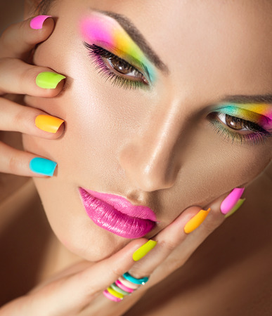 Krásná dívka tvář s živým make-up a barevné laky na nehty