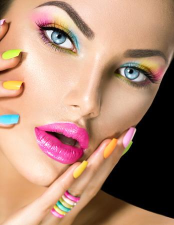 Beauty girl face with vivid makeup and colorful nail polish
