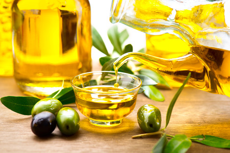 Aceite de oliva virgen verter en un cuenco de cerca Foto de archivo
