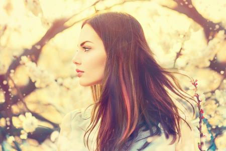 divat: Gyönyörű modell lány hosszú fúj hajat tavaszi kert