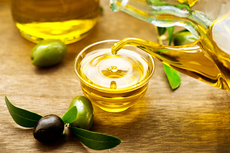 Virgin olive oil pouring in a bowl close up Imagens