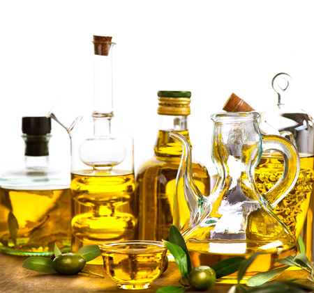 foglie ulivo: Olio d'oliva. Bottiglie e barattoli di olio extra vergine d'oliva su bianco Archivio Fotografico
