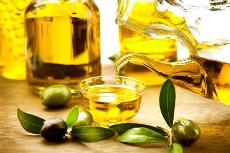 hoja de olivo: Aceite de oliva virgen verter en un cuenco de cerca Foto de archivo