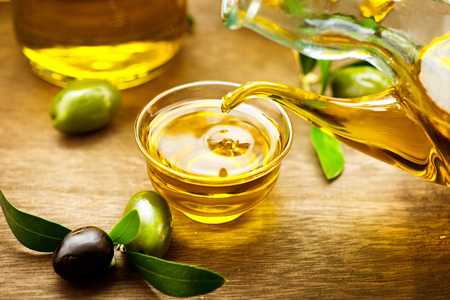 mediterranean cuisine: Virgin olive oil pouring in a bowl close up Stock Photo